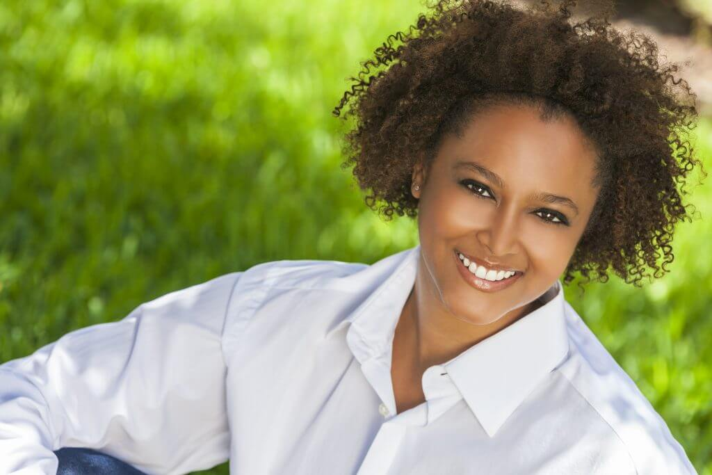 Beautiful young African American woman with perfect teeth smiling and relaxing outside in summer sunshine Platelet Rich Plasma Treatments can be ideal for hair loss in african american women