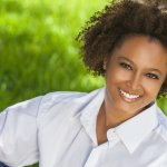 Female Hair Loss Beautiful young African American woman with perfect teeth smiling and relaxing outside in summer sunshine Platelet Rich Plasma Treatments can be ideal for hair loss in african american women